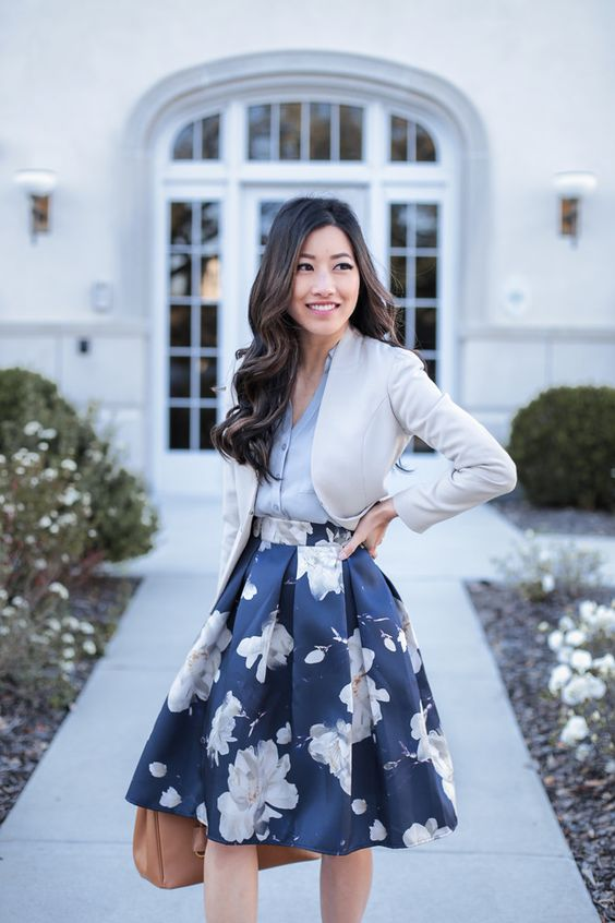 a full navy floral print skirt, a grey v-neck shirt, a cropped creamy jacket and a brown bag