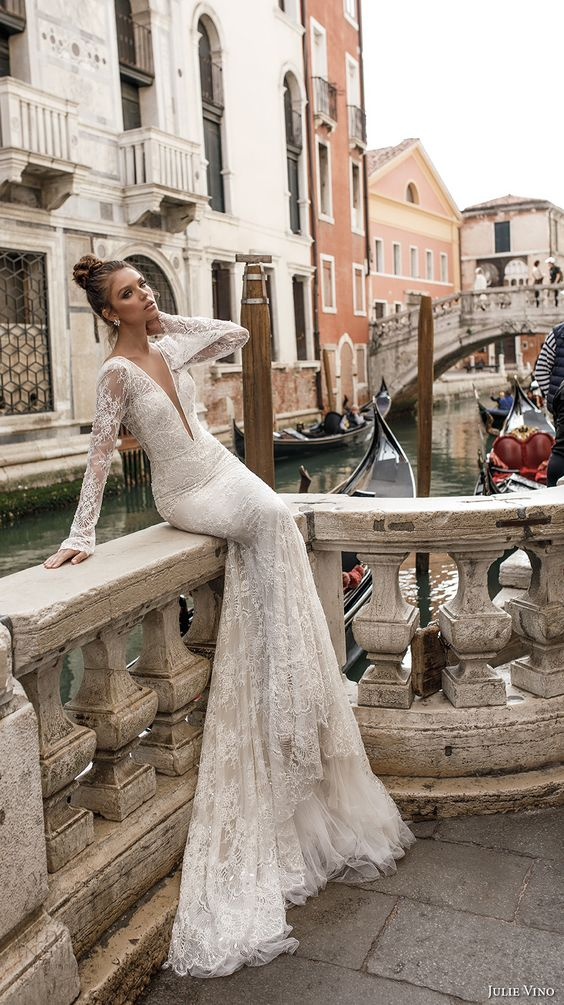 a mermaid wedding gown with a plunging neckline, lace appliques, long sleeves and embellishments by Julie Vino