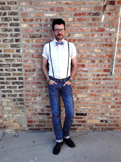 With white shirt, bow tie, cuffed jeans and black boots