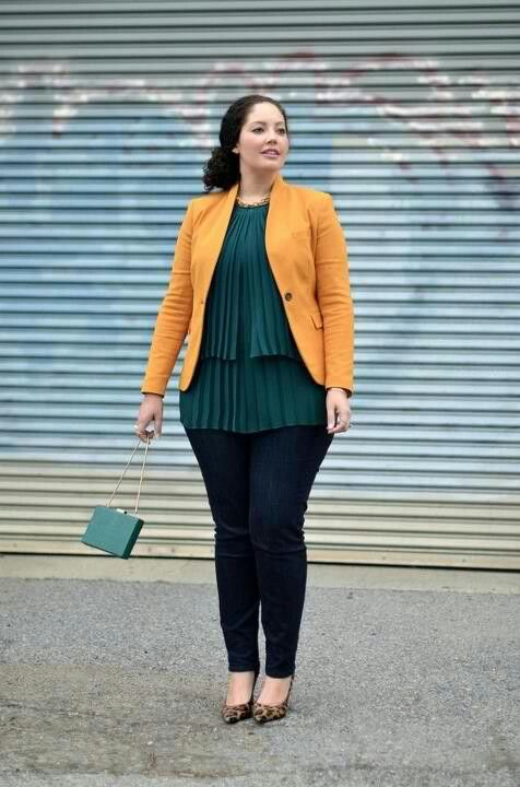 a colorful look with navy skinnies, a dark green pleated layered top, a yellow jacket and a bag