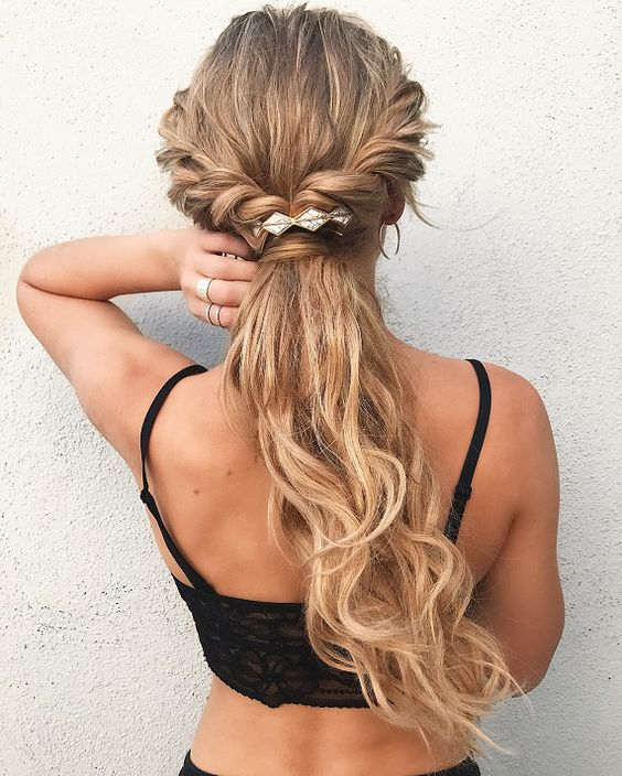 a twisted braided half up ponytail accented with a geometric hairpiece