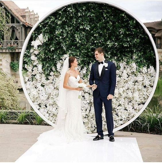a minimalist wedding backdrop with greenery and white blooms is a chic statement