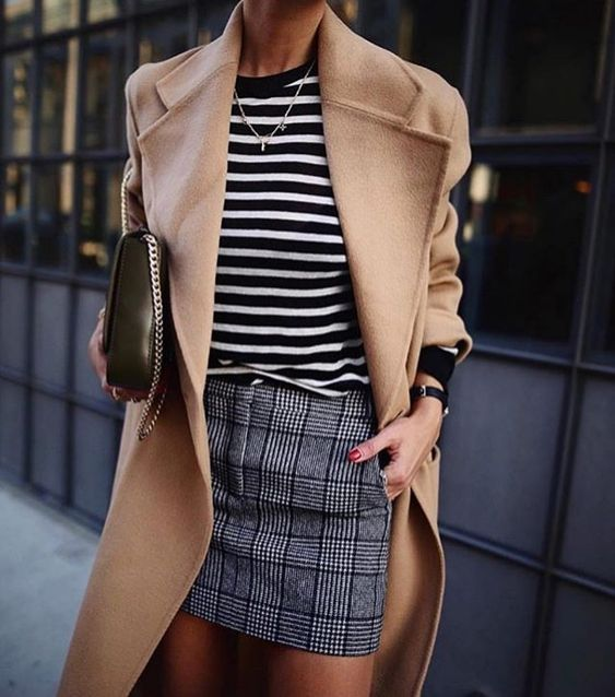 a checked mini skirt, a black and white striped top, a camel coat and a black bag