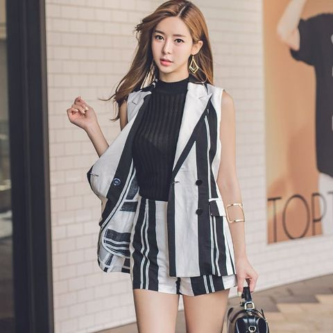 With black top, striped shorts and black leather bag
