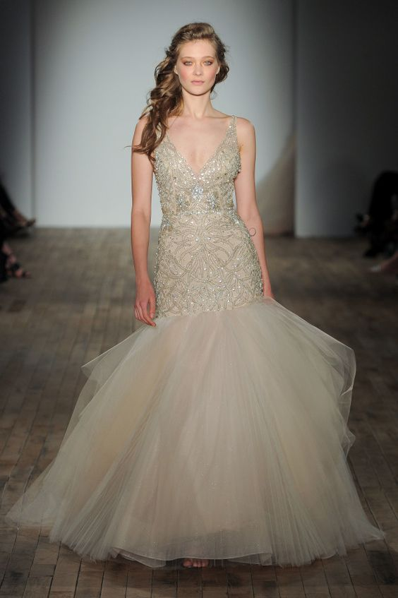 a champagne colored heavily embellished wedding dress with a tail and an embroidered bodice on straps by Lazaro