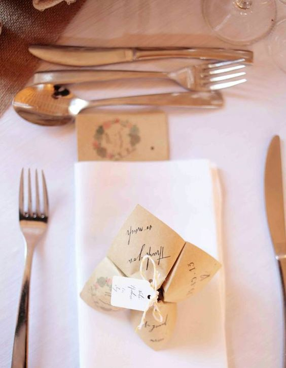 a origami wedding proglam or menu made of craft paper and with a tag and yarn for a rustic wedding