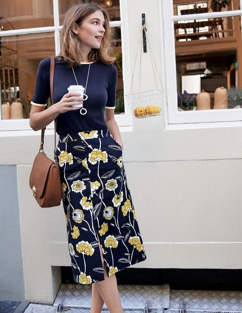 a navy floral print midi skirt, a navy top, a brown bag for a modest work look