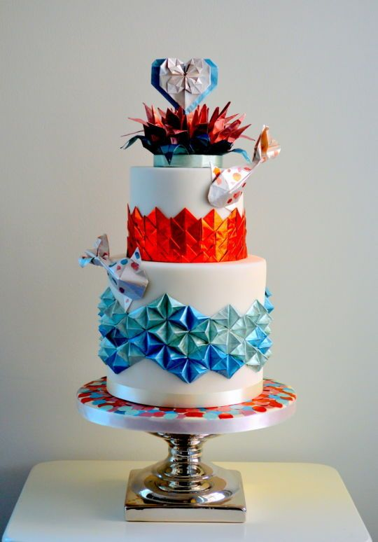 a colorful wedding cake decorated with origami and koi fish for a quirky Japanese wedding