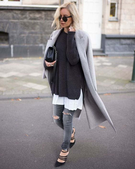 a white tee, a black sweater, a grey coat, grey ripped denim and black strappy shoes