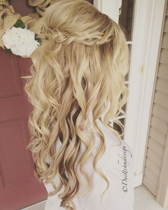 half up half down hairstyle with waves and a small braid going as a halo