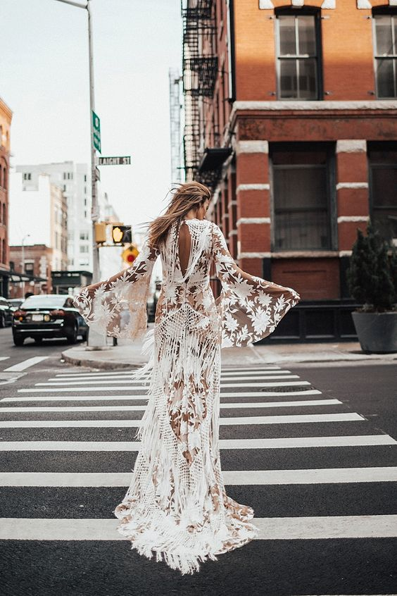 a sheer and boho lace applique wedding dress with bell sleeves and a cutout back