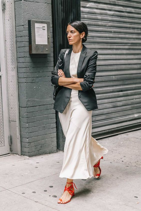 a long black blazer, a neutral midi dress, red strappy sandals for a colorful touch