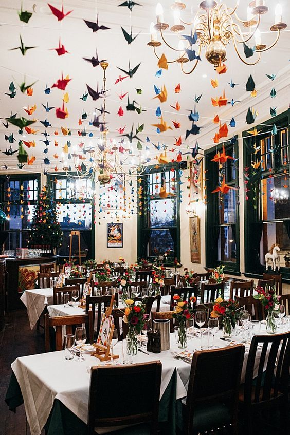 colorful paper cranes hanging over the whole wedding reception