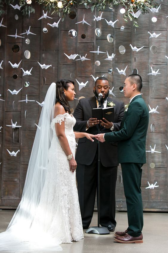 a wedding backdrop made of paper cranes and couple's photos plus greenery on top