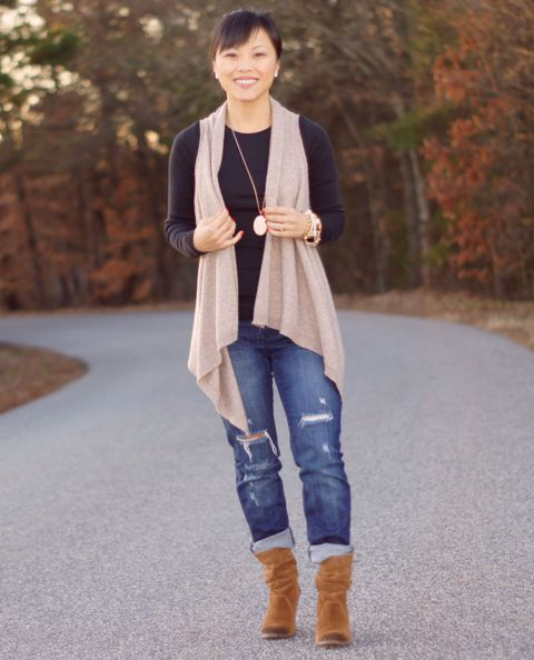 With black shirt, distressed jeans and brown suede mid calf boots