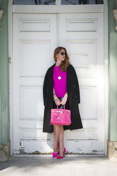 a black knee skirt, a hot pink top and shoes, a pink bag, a black coat