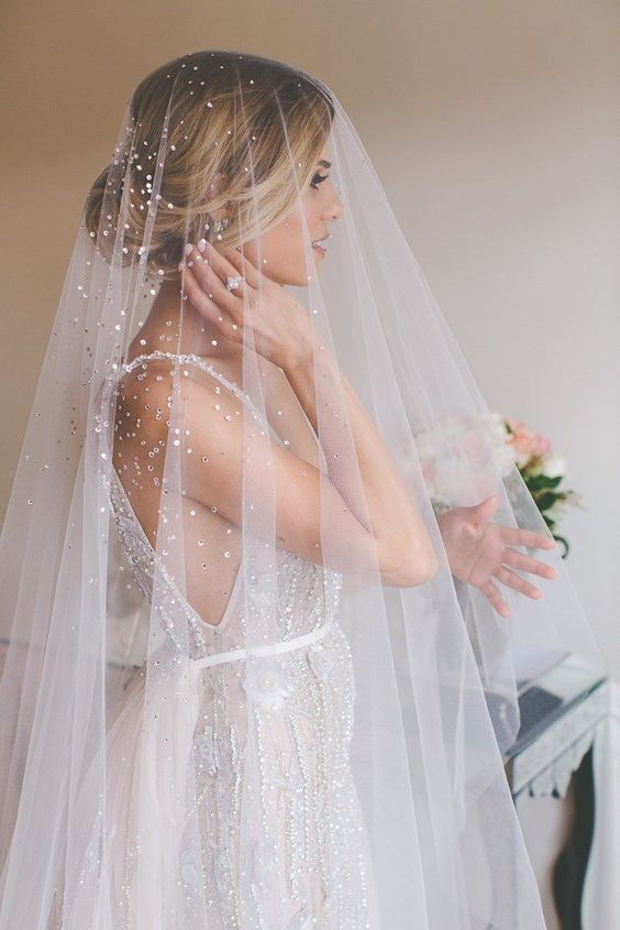 a gorgeous beaded veil worn with a beaded wedding gown adds a glam feel to the look
