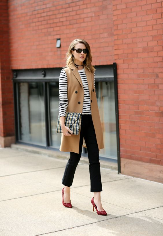 black pants, a striped top with long sleeves, a camel long vest and red shoes