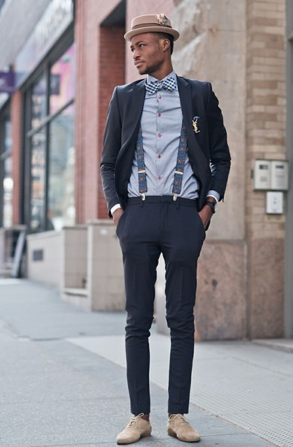 With light blue shirt, checked bow tie, navy blue pants, light gray suede shoes, navy blue blazer and hat
