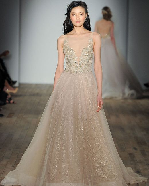 champagne-colored illusion plunging neckline wedding dress with an embellished bodice and a sparkly skirt by Lazaro