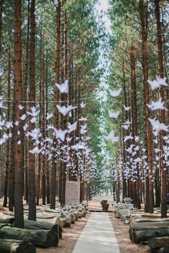a woodland wedding ceremony space with lots of paper cranes and wooden trunks