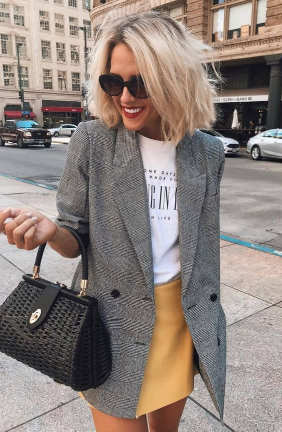 a yellow mini skirt, a printed tee, a checked grey blazer, a black bag for a chic casual look