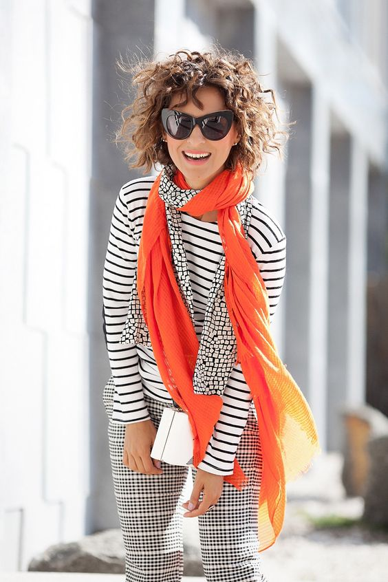 a striped black and white top, checked pants, an orange and printed scarf as an accent