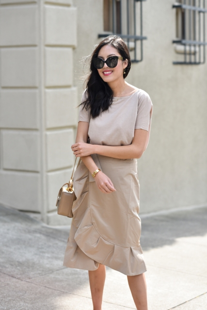 With beige shirt and beige leather mini bag