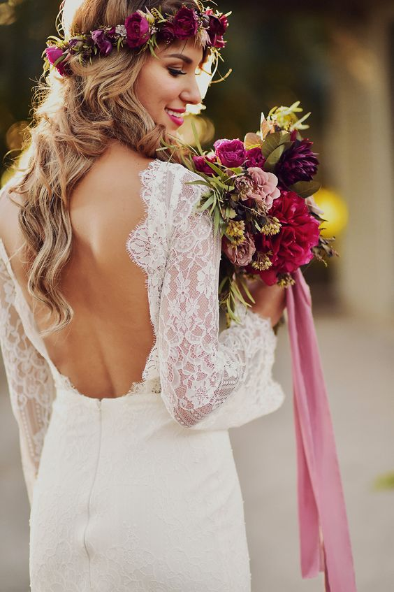 a lace sheath bell sleeve wedding dress with an open back for a boho bride