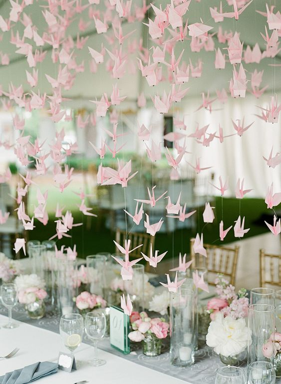 pink paper crane garlands hanging over the wedding reception for creating an ambience