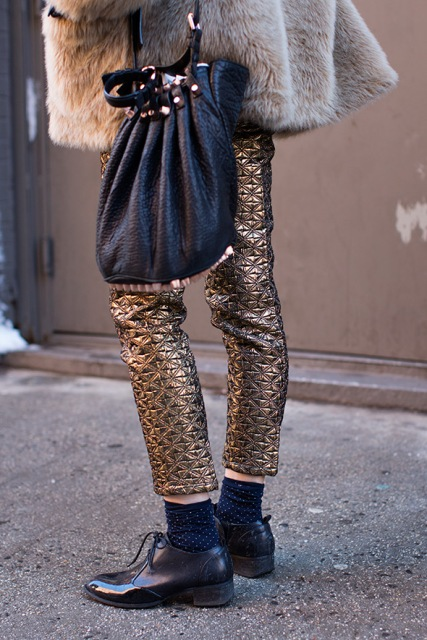 With fur coat, black bag and flat shoes