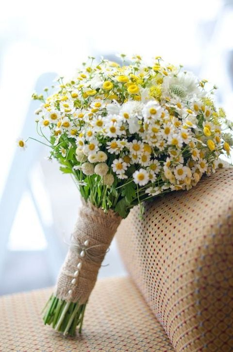 a rustic bridal bouquet of wildflowers and with a burlap wrap with pearl pins