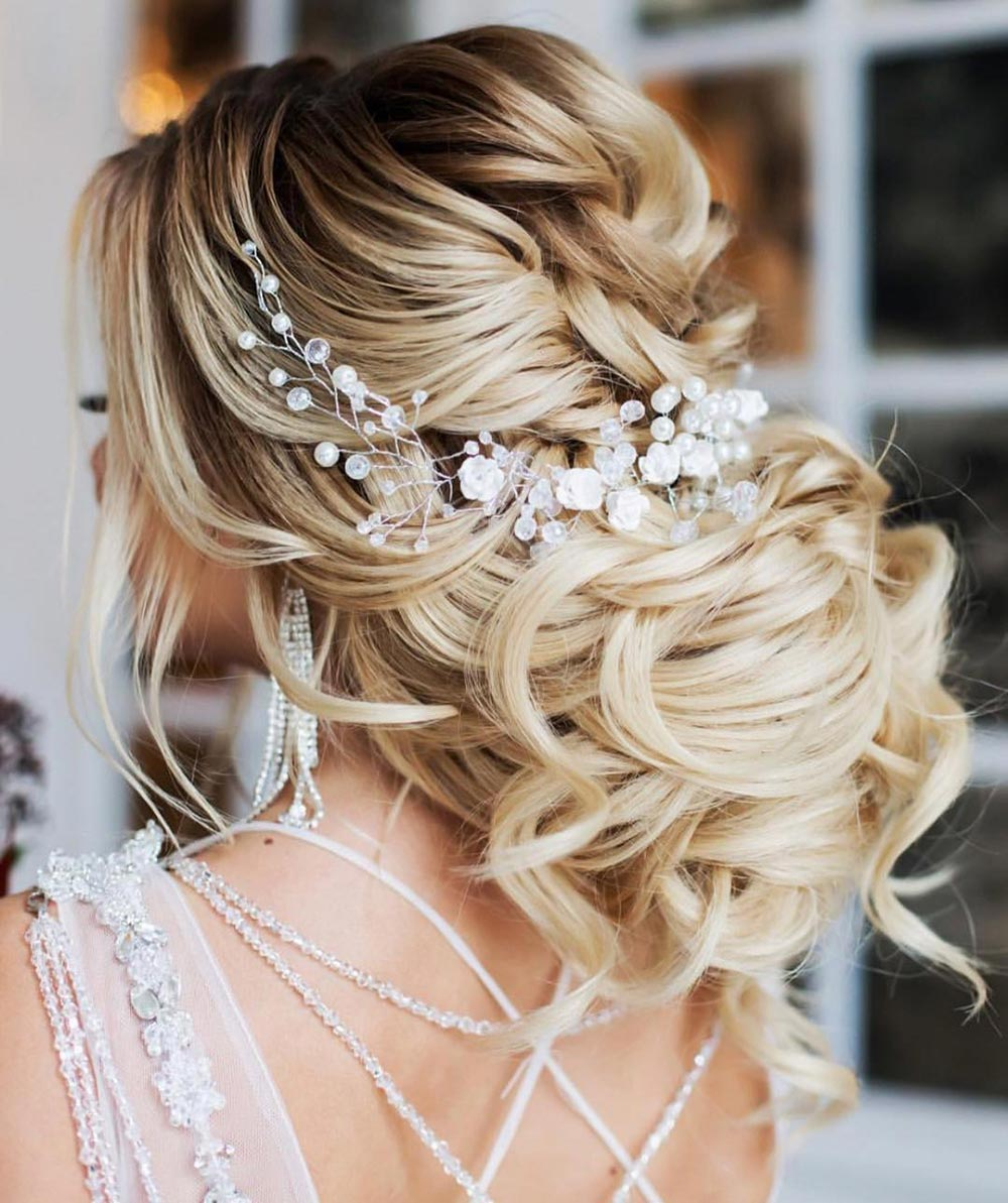 loose low bun wedding hairstyle with accessories