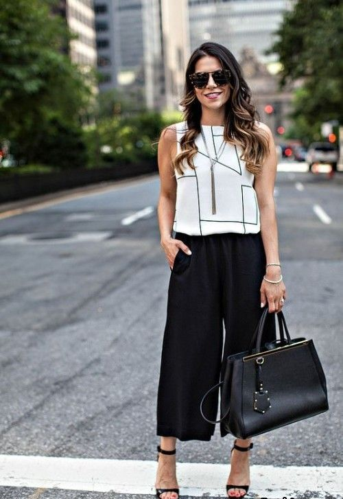 black culottes, a geometric black and white top, a black bag and black shoes