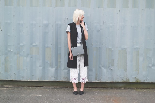 With gray t-shirt, long vest, gray bag and flats