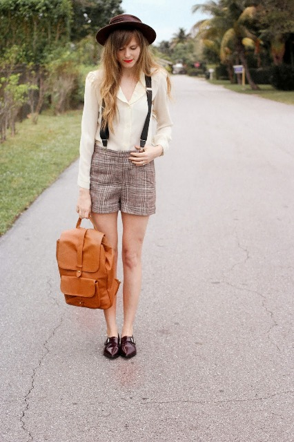 With beige shirt, wide brim hat, brown shoes and brown backpack