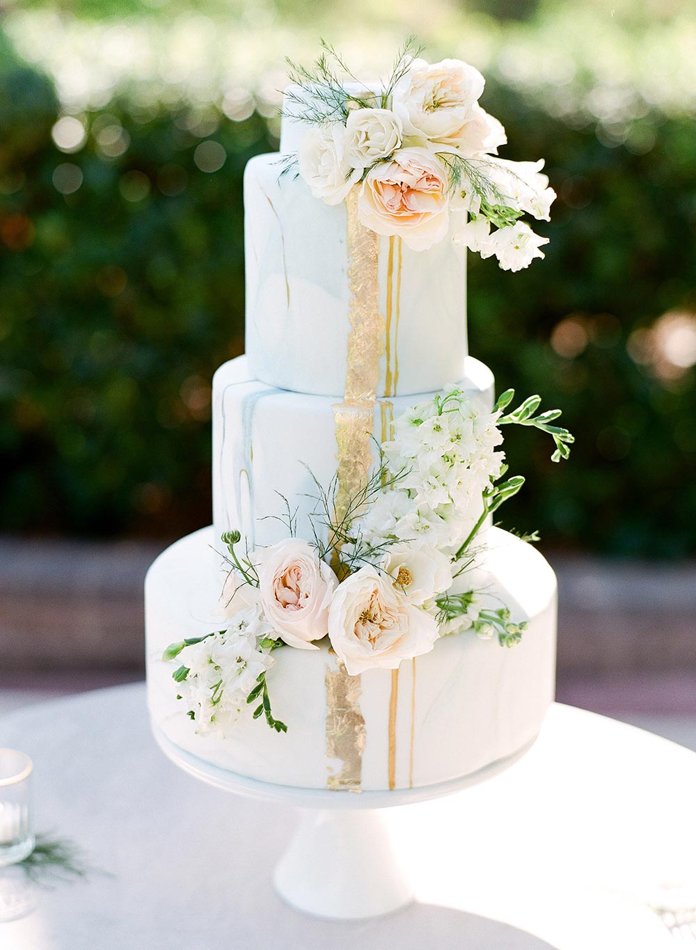 pale blue wedding cake with lush flowers and gold foil