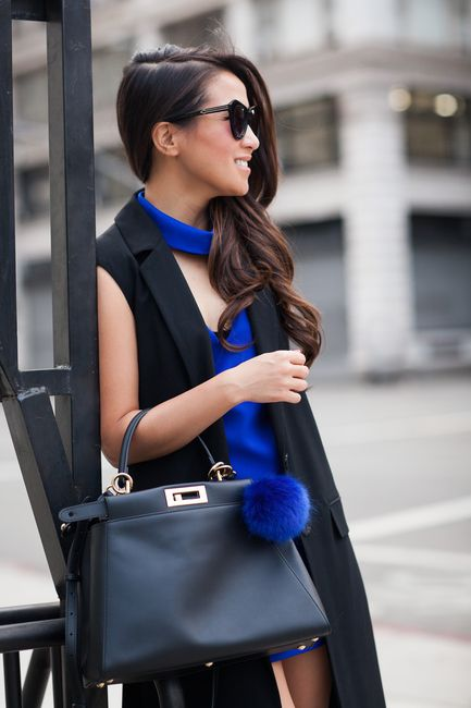 a black leather bag with a long strap and copper detailing plus a fluff