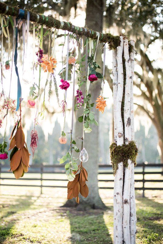 a boho wedding arch decorated with greenery and blooms hanging down from it