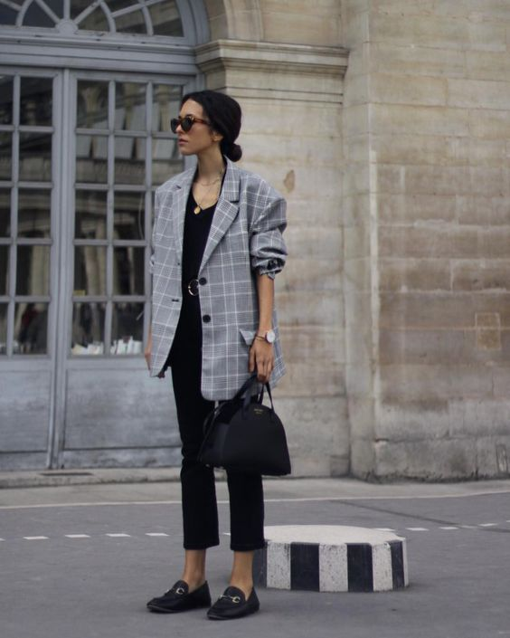 a black top, black cropped pants, an oversized checked blazer and a black bag