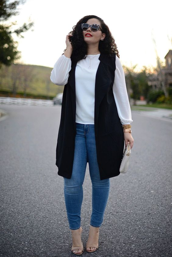 blue skinnies, a white blouse, a long black vest and nude shoes for a chic look