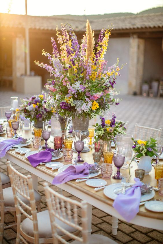 an exquisite table setting of lavender and yellow plus amber and grey touches with a very lush and textural centerpiece