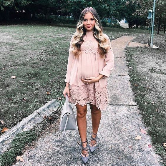 a blush lacey dress with long sleeves, a high neckline, grey suede strappy heels and a grey bag