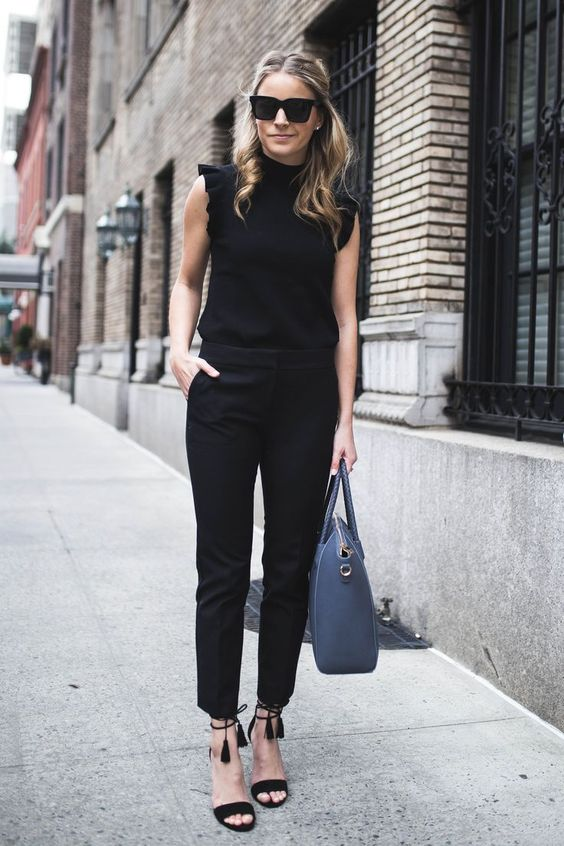 a black jumpsuit with a high neckline, ruffled sleeves, black tassel shoes and a blue bag for a casual business look