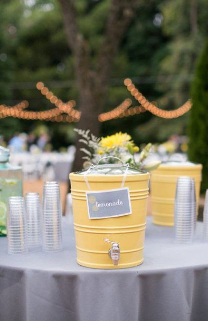 a grey table with a yellow lemonade tank for a rustic or woodland drink station