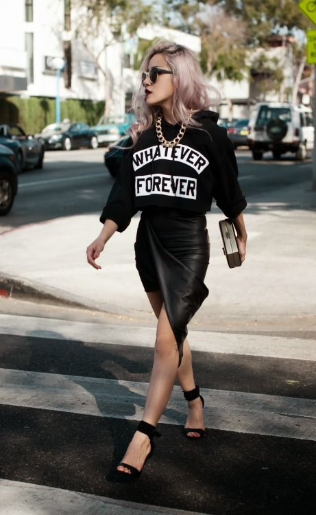 a black printed sweatshirt, a black leather asymmetrical skirt, black shoes and a statement chain necklace