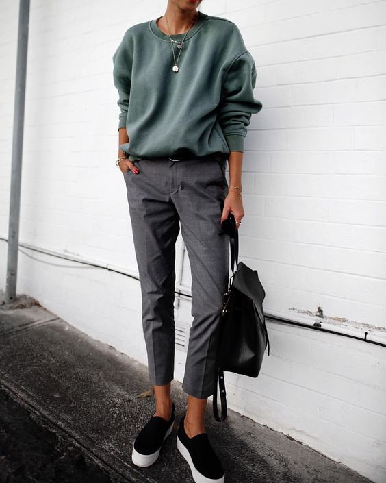 an olive green sweatshirt, cropped grey trousers, black slipons and a black backpack