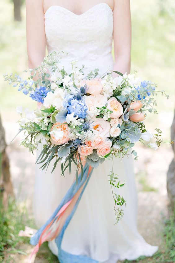 a lush peachy pink and blue wedding bouquet with long ribbons for a bold summer look