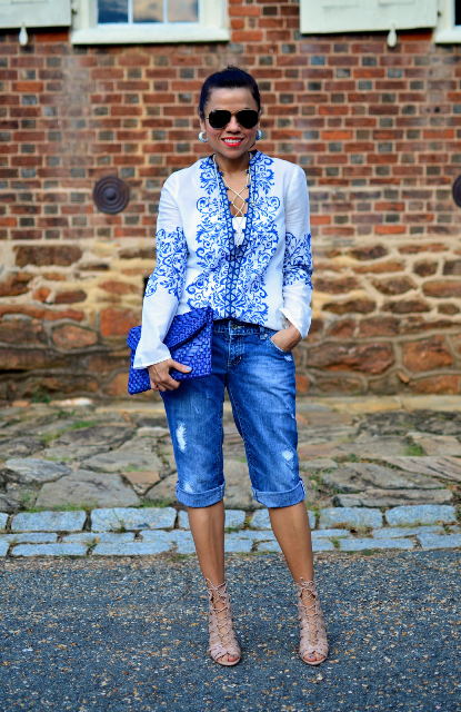With printed blouse, beige lace up sandals and blue clutch