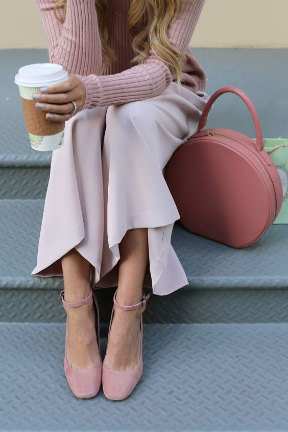 a pink round bag continues the pink theme of the outfit and adds a soft touch